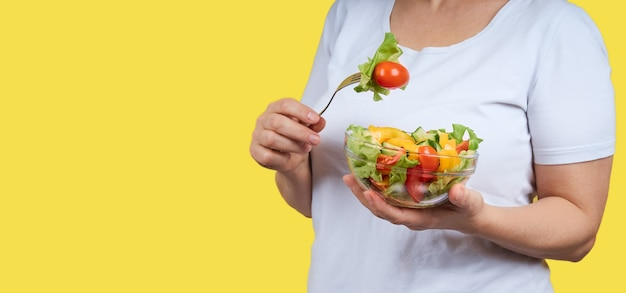 Image recadrée de femme en chemise blanche tenant une assiette de salade de légumes