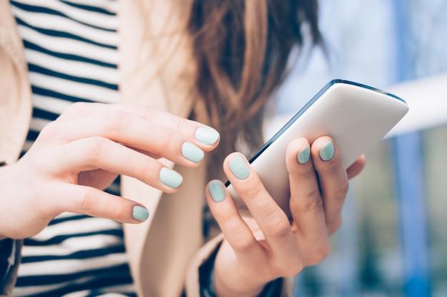 Image recadrée d'une femme dans un manteau beige tenant un téléphone portable dans ses mains