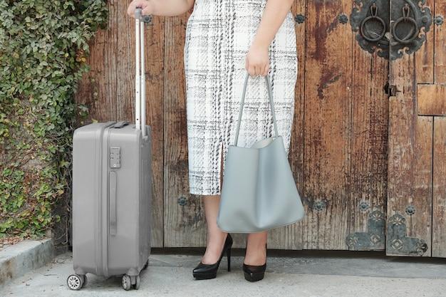 Image recadrée d'une femme debout à l'extérieur avec une grosse valise et un sac en cuir en attente de taxi