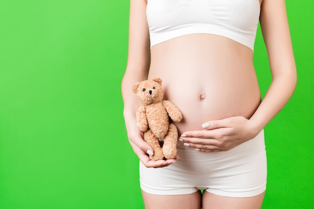Image recadrée d'une femme enceinte heureuse en sous-vêtements blancs tenant un ours en peluche contre son ventre
