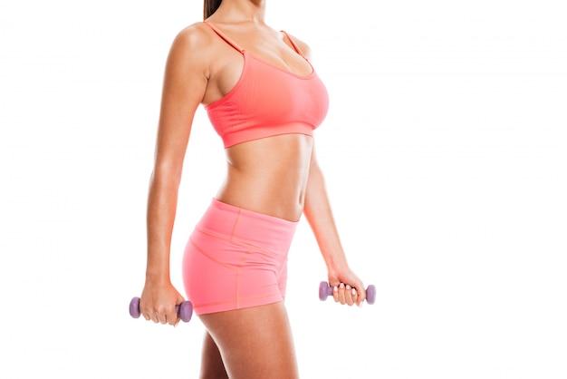 Image recadrée d'une femme fitness en tenue de sport tenant des haltères