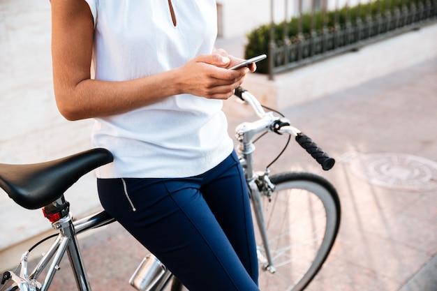 Image recadrée d'une femme heureuse en tapant mesaage sur le smartphone s'appuyant sur un vélo dans la rue