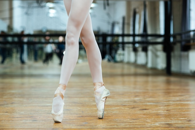 Image recadrée d'une femme jambes en pointes debout sur les orteils