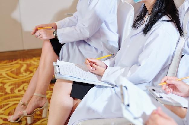 Image recadrée de femme médecin prenant des notes sur une feuille blanche lors de la participation à une conférence pour les travailleurs médicaux