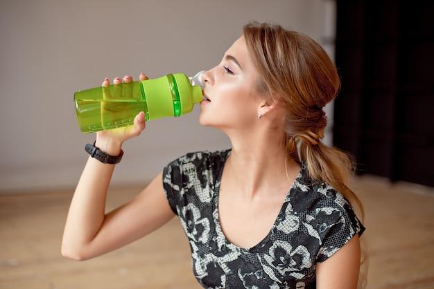 Image recadrée de femme sportive tenant une bouteille d'eau.