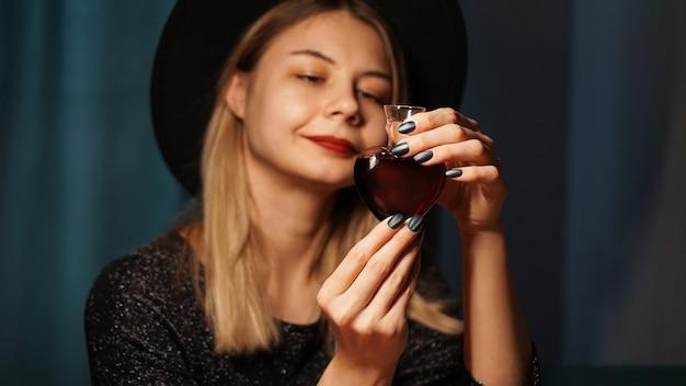 Image recadrée d'une femme tenant un pot en verre en forme de coeur de philtre d'amour. belle jeune femme au chapeau de sorcière. concentrez-vous sur la potion ou la fiole de poison