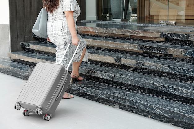 Image recadrée d'une femme avec une valise qui monte les escaliers d'un hôtel spa chic