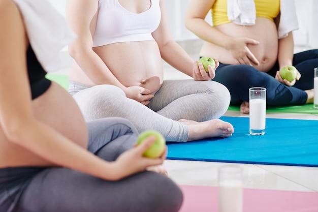Image recadrée de femmes enceintes assises sur des tapis de yoga et ayant des pommes vertes et du yaourt frais après avoir médité ensemble