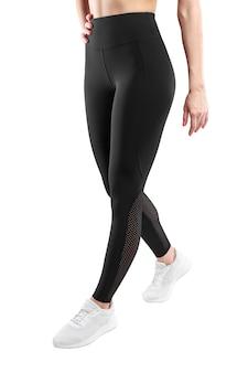 Image recadrée d'une figure féminine dans des leggings noirs serrés prendre un pas de côté, sur fond blanc. vue verticale.