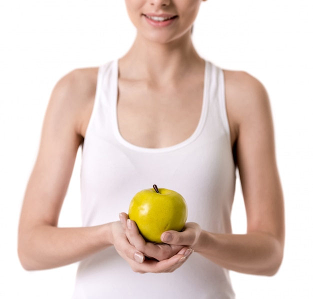 Image recadrée de fille tenant une pomme et souriant. concept de régime