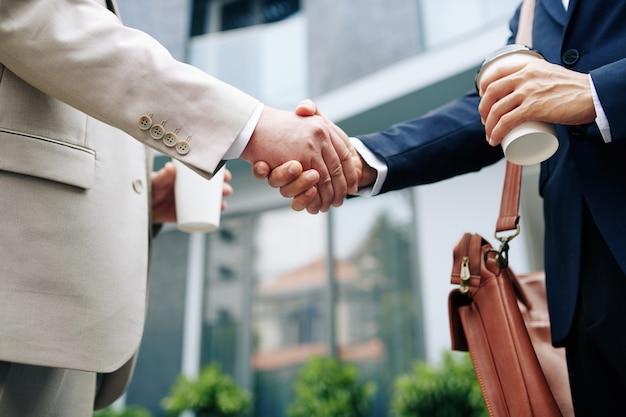 Image recadrée de gens d'affaires avec une tasse de café à emporter se serrant la main et se saluant