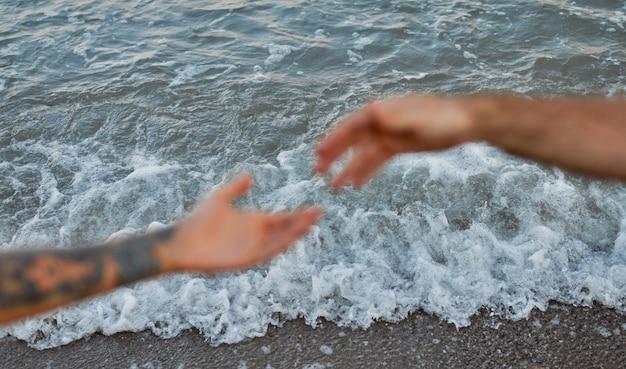 Image recadrée en gros plan des mains d'un jeune couple sur fond de mer et de vagues qui s'étendent l'une vers l'autre.