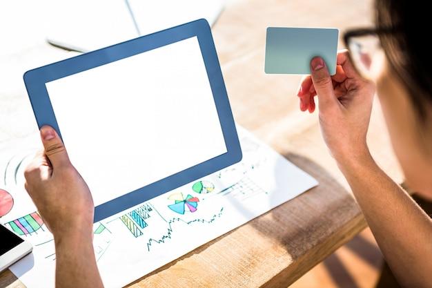 Image recadrée d'homme d'affaires hipster avec tablette et carte de crédit au bureau
