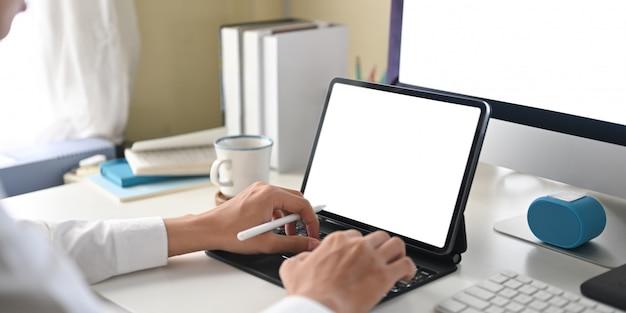 Image recadrée d'un homme d'affaires utilise une tablette informatique à écran blanc blanc au bureau de travail blanc.