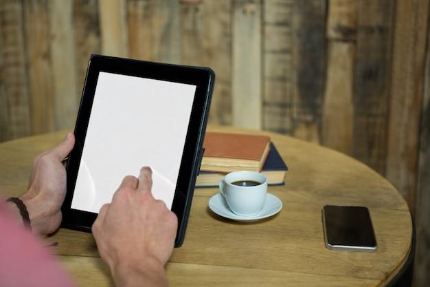 Image recadrée de l'homme à l'aide de tablette numérique avec écran vide dans un café