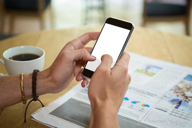 Image recadrée de l'homme à l'aide de téléphone portable à table dans un café