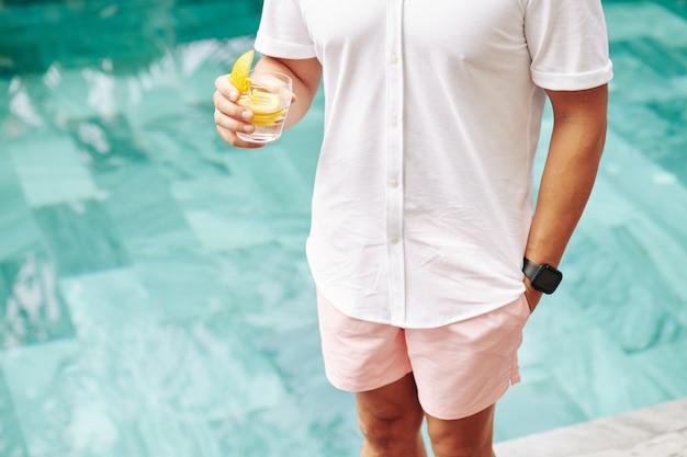 Image recadrée de l'homme en chemise et short rose debout près de la piscine et boire du gin tonic
