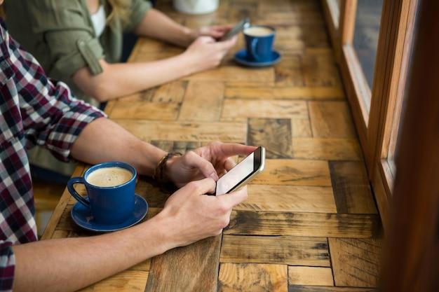 Image recadrée de l'homme et de la femme à l'aide de téléphones mobiles dans un café