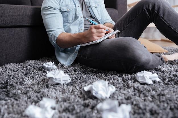 Image recadrée d'un homme prenant des notes dans le bloc-notes alors qu'il était assis sur un tapis avec du papier brouillé autour
