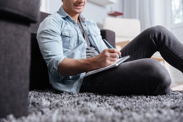 Image recadrée d'un homme en tenue décontractée écrivant dans un cahier alors qu'il était assis sur le tapis à la maison