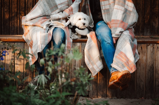 Image recadrée de jeune couple assis dans un parc en couverture avec chien blanc entre eux