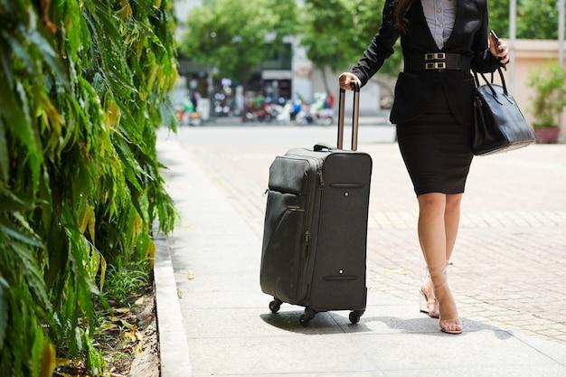 Image recadrée d'une jeune femme d'affaires élégante marchant dans la rue jusqu'au bâtiment de l'hôtel avec une grosse valise