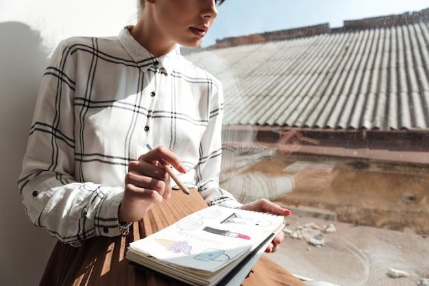Image recadrée d'une jeune femme artiste dessinant des croquis