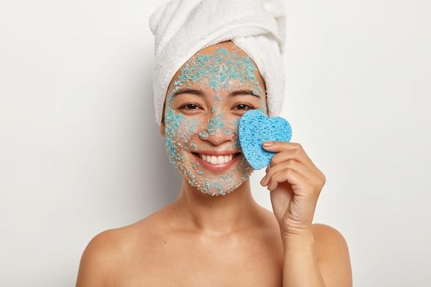 Image recadrée d'une jeune femme heureuse tient une éponge cosmétique en forme de coeur, applique un masque de gommage naturel bleu, a un large sourire, une serviette enveloppée sur la tête, se tient les épaules nues à l'intérieur. concept de soins spa