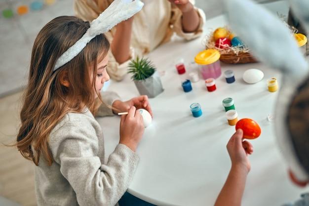 Image recadrée d'une jeune femme avec une petite fille et un garçon mignons se préparent pour la célébration de pâques. une famille heureuse portant des oreilles de lapin passe du temps ensemble avant pâques tout en peignant des œufs.