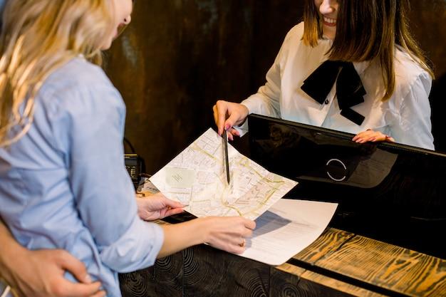 Image recadrée de jeune femme réceptionniste donnant des informations touristiques