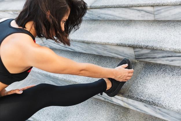 Image recadrée d'une jeune femme sportive faisant des exercices d'étirement à l'extérieur