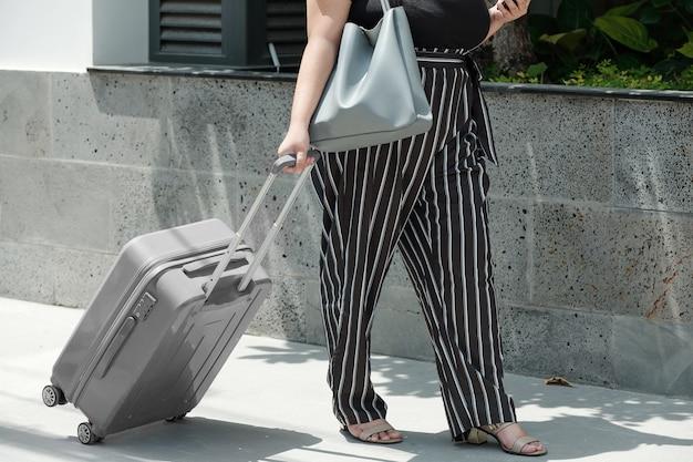 Image recadrée d'une jeune femme de taille plus marchant avec une valise jusqu'à la gare et vérifiant le chemin via l'application sur smartphone