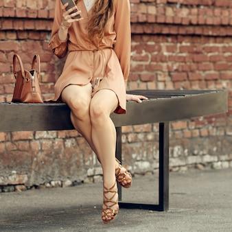 Image recadrée d'une jeune fille en robe courte avec les jambes nues en sandales assis sur un banc avec un téléphone mobile à la main