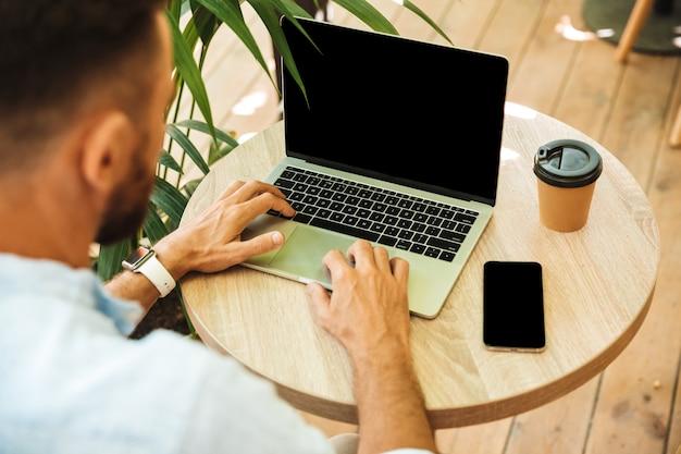 Image recadrée de jeune homme barbu utilisant un ordinateur portable