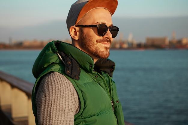 Image recadrée de jeune homme gai à la recherche amicale dans des lunettes de soleil