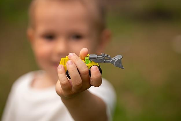 Image recadrée de la main des enfants tenant une voiture jouet mise au point sélective