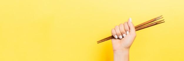 Image recadrée de main féminine tenant des baguettes en poing sur jaune.