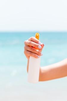 Image recadrée d'une main de femme tenant un spray solaire au fond de la mer.