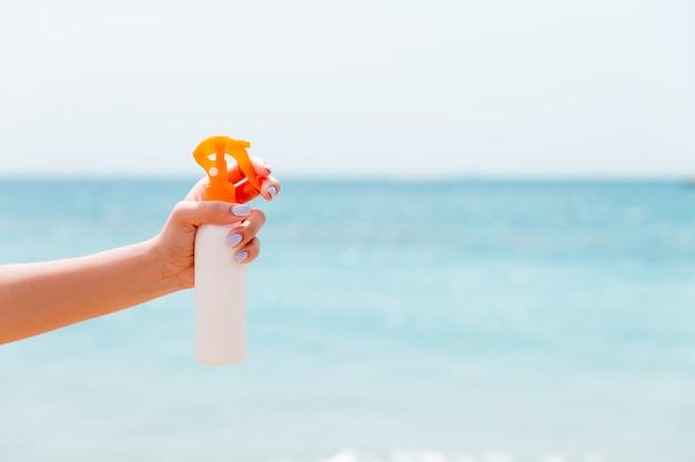 Image recadrée d'une main de femme tenant un spray solaire à la plage.