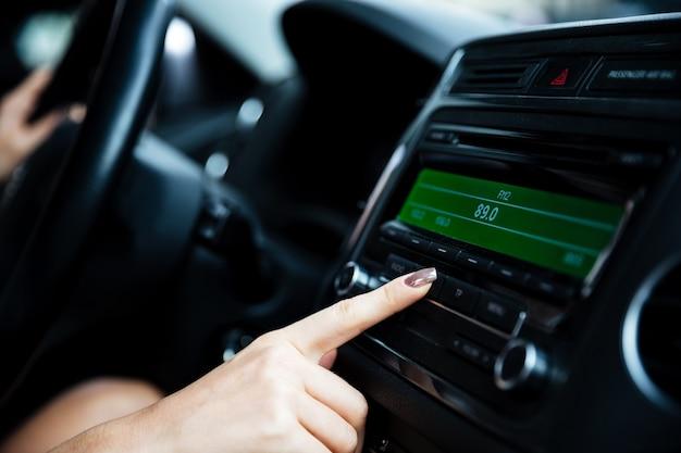 Image recadrée d'une main de femme tournant le bouton de la radio en voiture