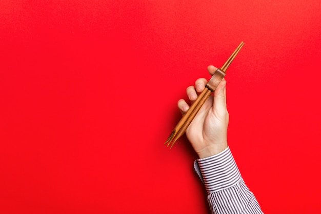 Image recadrée de la main masculine tenant des baguettes