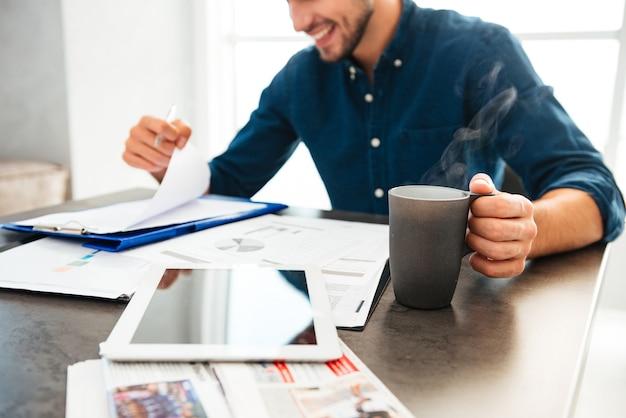 Image recadrée des mains du jeune homme tenant des documents et une tasse de café