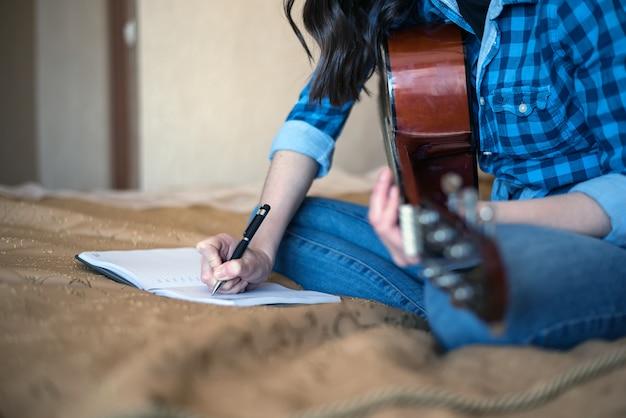 Image recadrée de mains féminines écrivant dans un cahier avec une guitare acoustique
