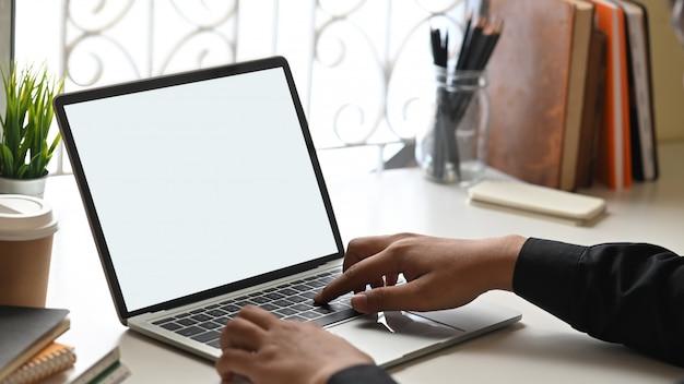 Image recadrée de mains d'homme d'affaires tapant sur un ordinateur portable avec un écran blanc blanc qui met en place un bureau de travail ordonné entouré de livres, d'un porte-crayon, d'une tasse à café et d'une plante en pot.