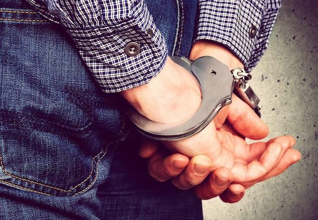 Image recadrée de mains masculines menottées derrière le dos