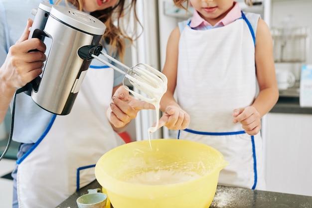 Image recadrée de mère et fille dégustant de la crème sucrée qu'ils ont faite pour le gâteau