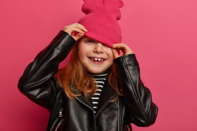 Image recadrée de la petite fille regarde du chapeau, cache le visage, porte une veste en cuir noir élégante, vêtue de vêtements à la mode a un look ambitieux positif isolé sur un mur rose. enfants, émotions, style