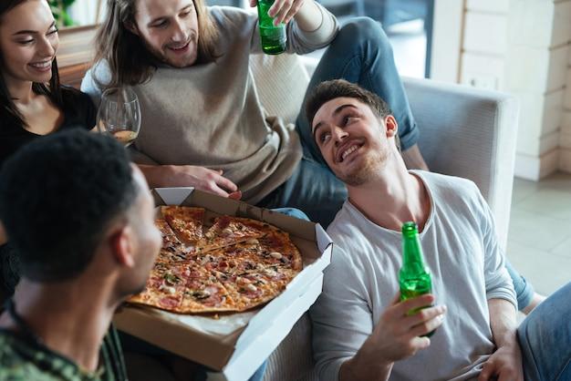 Image recadrée de quatre amis assis avec pizza
