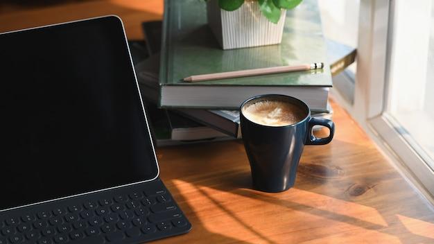 Image recadrée de tablette informatique avec étui à clavier mettant sur une table en bois avec tasse de café