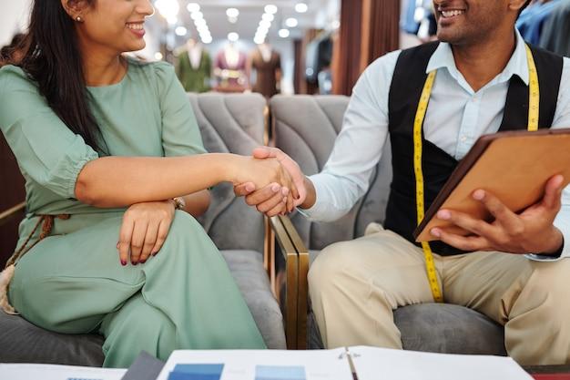 Image recadrée d'un tailleur et d'une cliente se serrant la main après une réunion en atelier